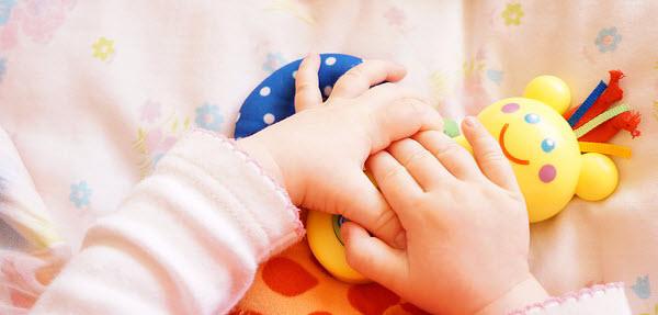 おもちゃで遊ぶ赤ちゃんの手